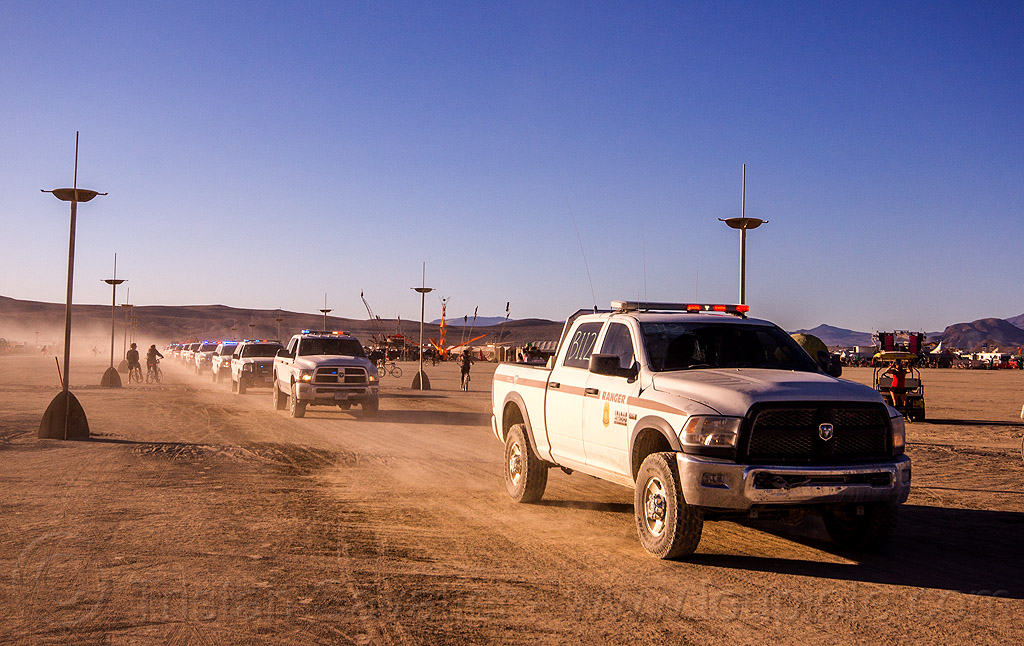 A procession of law enforcement cars converge to the temple for memorial to fallen officer - burning man 2015, blm, burning man, cars, cops, law enforcement officers, leo, memorial, park rangers, police, procession, sheriff, suv
