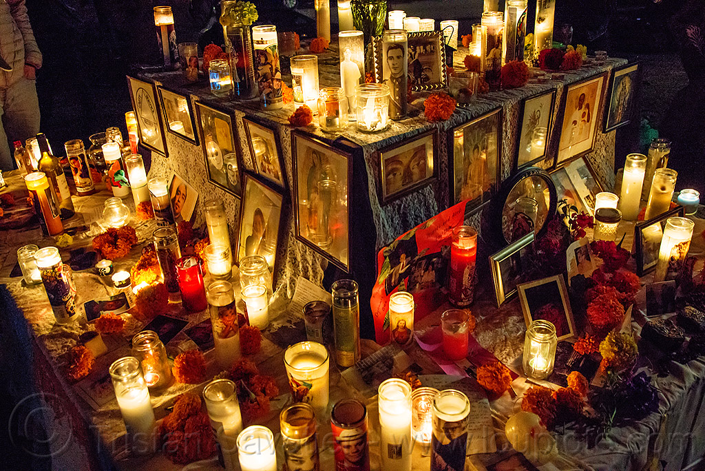 altar de muertos - glass candles - dia de los muertos, candle light, day of the dead, flowers, framed images, frames, halloween, marigold flowers, mementos, night