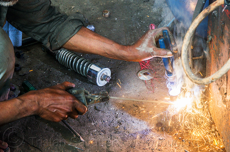 arc welding repair on motorbike shock (india), 350cc, arc welding, fixing, man, mechanic, motorcycle, repairing, royal enfield bullet, shock absorber, sikkim, sparks, thunderbird, welder, worker, working