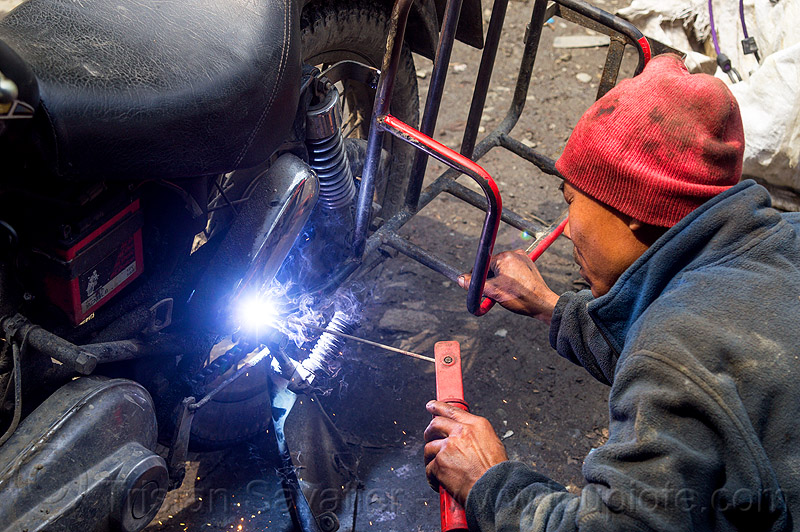 arc welding repair on motorcycle (india), 350cc, arc welding, fixing, luggage rack, man, mechanic, motorbike, motorcycle, repairing, royal enfield bullet, sikkim, thunderbird, welder, worker, working
