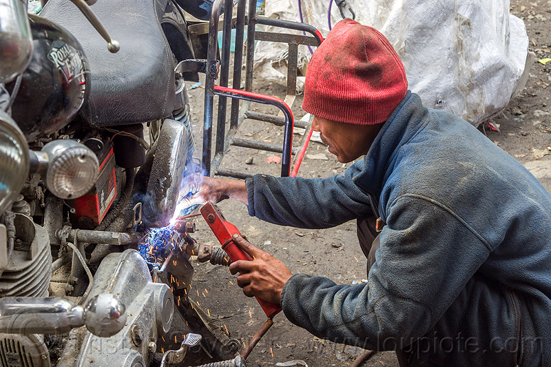 arc welding repair on royal enfield motorcycle rack (india), 350cc, arc welding, fixing, luggage rack, man, mechanic, motorcycle, repairing, royal enfield bullet, sikkim, sparks, thunderbird, welder, worker, working