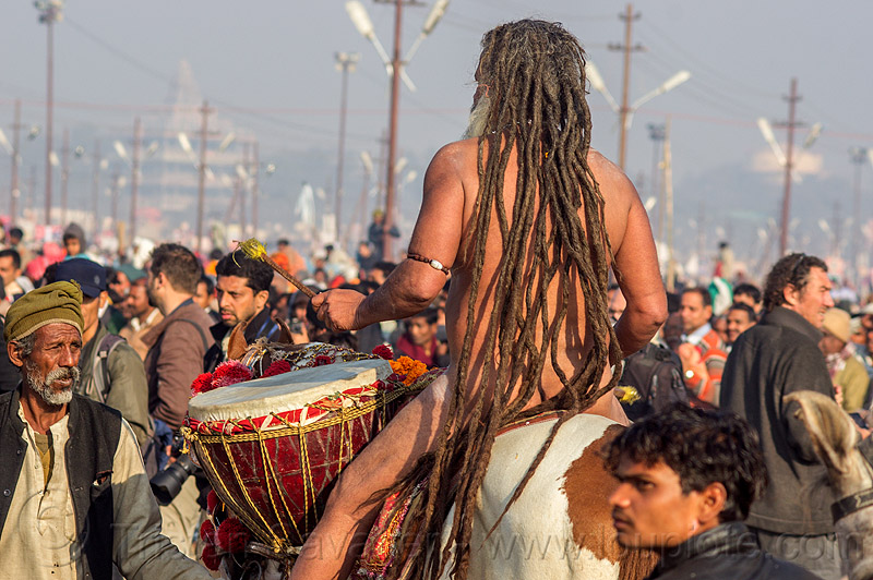 baba with long dreadlocks playing ritual drum on horse at kumbh mela (india), ceremony, crowd, dreadlocks, dreads, drums, hindu, hinduism, horse riding, horseback riding, kumbh maha snan, kumbha mela, maha kumbh mela, mauni amavasya, men, naga babas, naga sadhus, naked, procession
