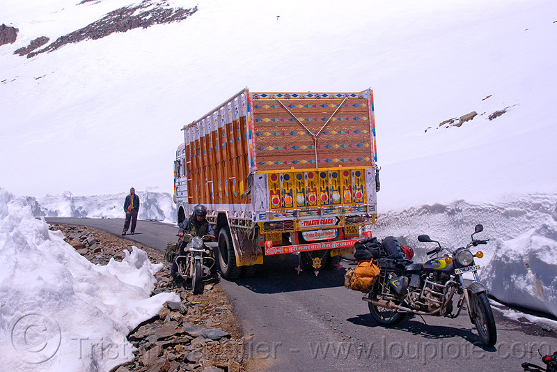 ben driving his motorcycle around a stalled truck - manali to leh road (india), baralacha pass, baralachala, ben, india, ladakh, lorry, motorcycle touring, mountain pass, mountains, rider, riding, road, royal enfield bullet, snow, truck