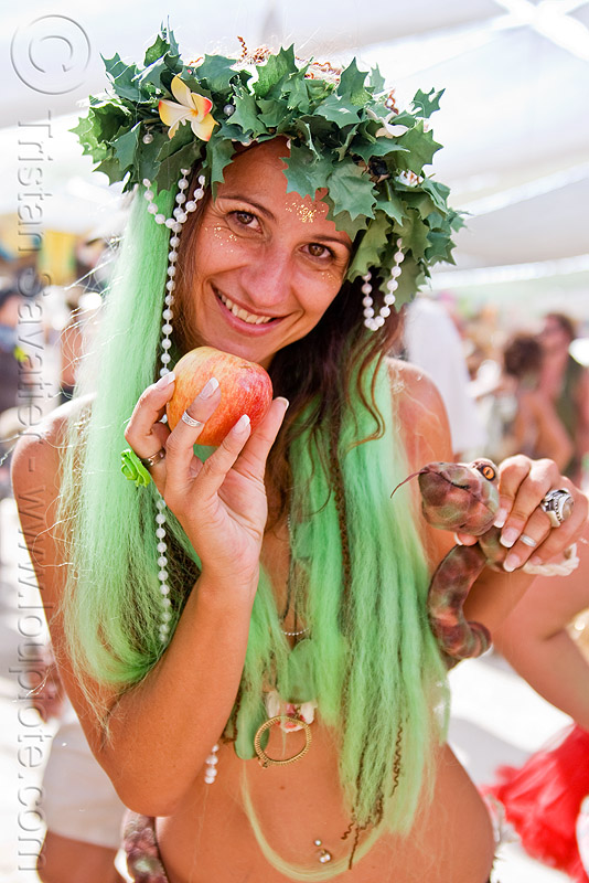 biblical eve with apple and snake, apple, biblical, burning man, center camp, crown, eve, green wig, headdress, headwear, leaves, maude, temptation, toy snake, woman