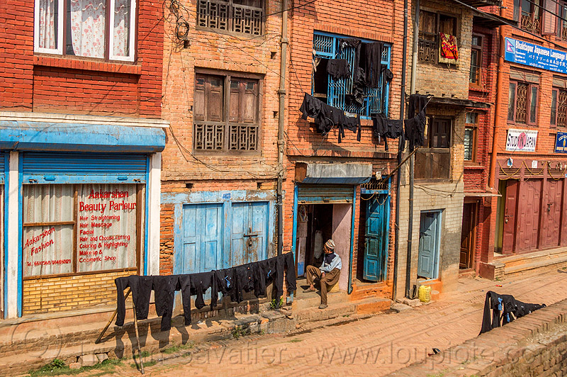 black dyed clothing drying on lines in street (nepal), bhaktapur, black, cloth line, drying, dyed, houses, man, sitting, street