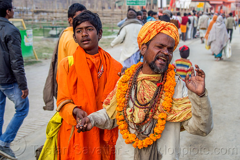 blind man singing and begging, beggar, begging, blind man, flower necklace, headdress, headwear, hindu, hinduism, holy beads, kumbha mela, maha kumbh mela, marigold flowers, men, necklaces, orange flowers, singing, street