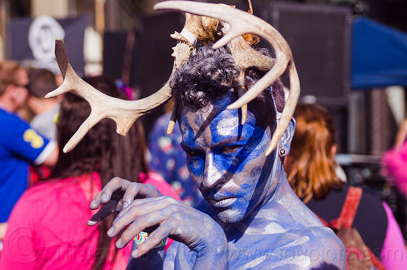 blue elf with antlers headdress, blue facepaint, festival, how weird festival, man, people