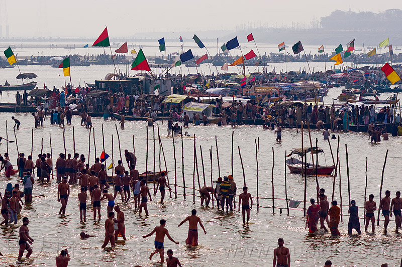 boats with flags and hindu pilgrims bathing in the ganges river at sangam - kumbh mela 2013 (india), backlight, colored flags, crowd, dawn, fence, ganga, ganges river, hindu pilgrimage, hinduism, holy bath, holy dip, india, maha kumbh mela, nadi bath, paush purnima, pilgrims, ritual bath, river bathing, river boats, silhouettes, triveni sangam