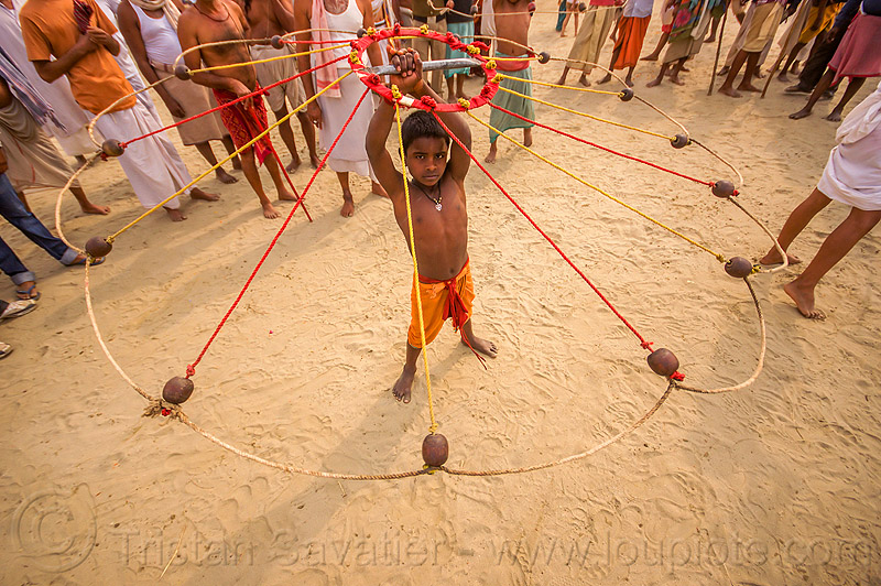 boy spinning balls with ropes (india), boy, game, hindu, hinduism, indian spinning balls, kumbha mela, maha kumbh mela, metal balls, performer, ropes