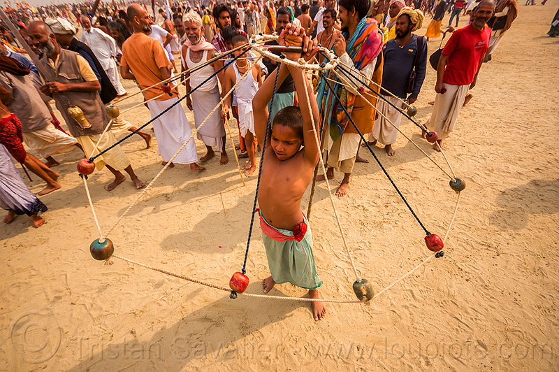 boy spinning colored balls with ropes (india), boy, crowd, game, hindu pilgrimage, hinduism, india, indian spinning balls, maha kumbh mela, metal balls, performer, ropes, spectators