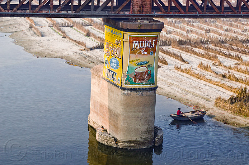 bridge pillar in ganga river - murli tea painted ad (india), advertising, agriculture, boat, floodplain, ganges, ganges river, metal bridge, people, river boat, riverbed, rowing boat, sand, small boat, truss, truss bridge, water