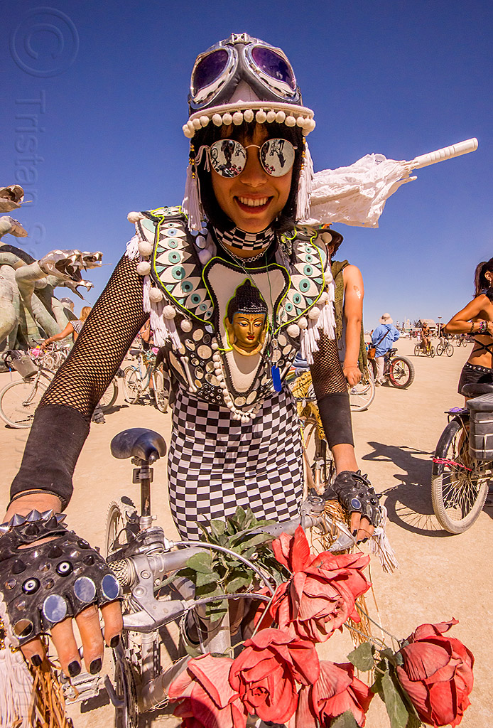 buddha costume - burning man 2015, bicycle, checkered dress, fingerless gloves, goggles, people, riding, sunglasses, white umbrella, woman