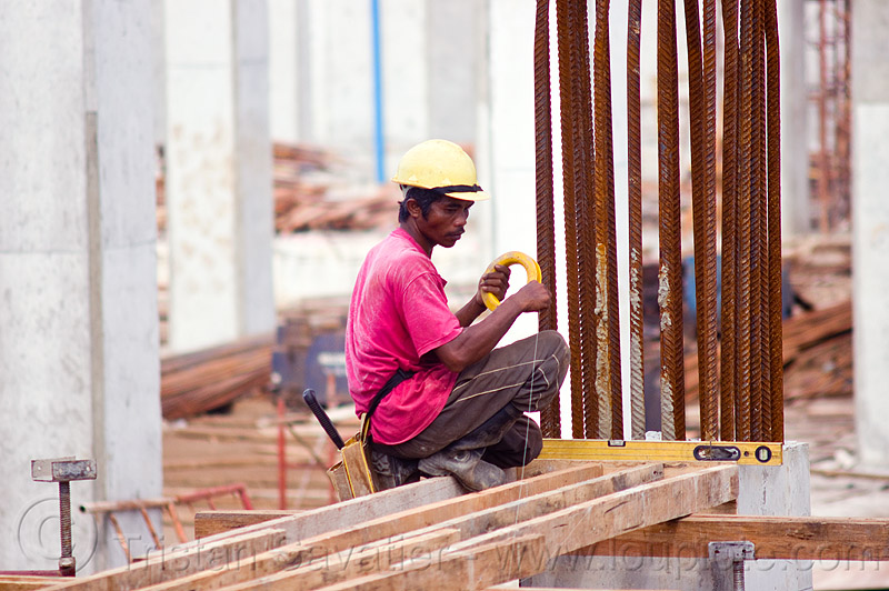 building timber shoring, borneo, bubble level, building construction, concrete forms, concrete wall forms, construction site, construction workers, formwork, lumber, malaysia, man, miri, nylon wire, rebars, safety helmet, scaffolding, shoring, sitting, spirit level, timber