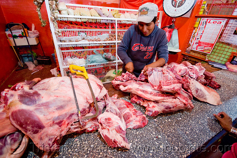 butcher selling llama meat, butcher, hack saw, llama meat, man, meat market, meat shop, noroeste argentino, quebrada de humahuaca, raw meat, tilcara
