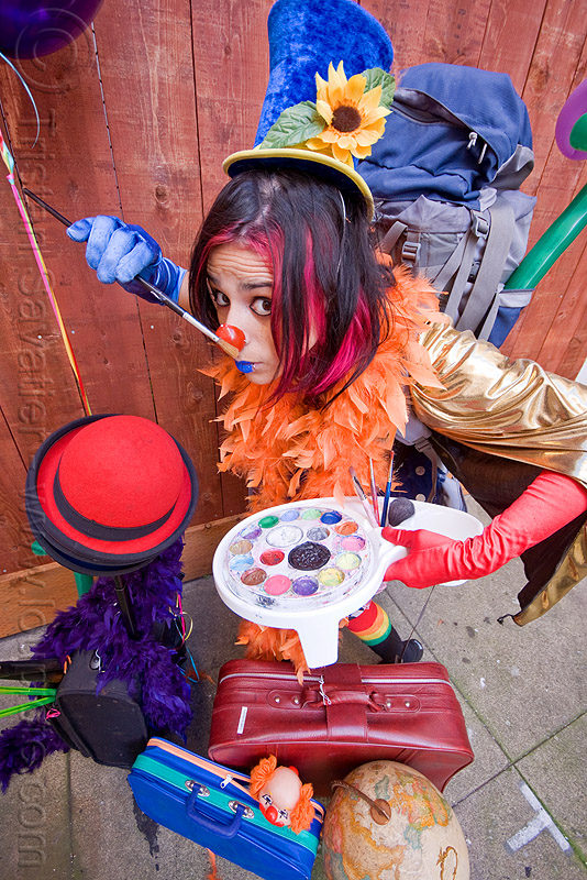 clown act, blue lipstick, bowler hat, circus artist, clown hat, clown nose, cocktail hat, feather boa, globe, luggage, mumu, paint brush, paint palette, party balloons, performer, props, suitcases, woman