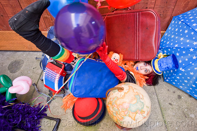 clown act - mumu circus performer, blue lipstick, bowler hat, circus artist, clown hat, cocktail hat, feather boa, globe, luggage, party balloons, performer, props, suitcases, woman