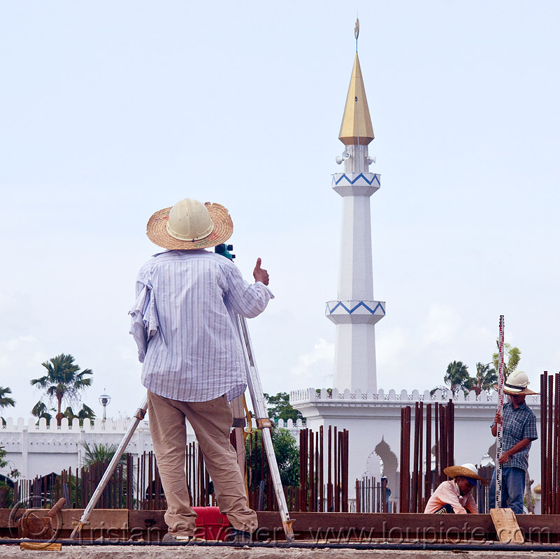 construction surveying - theodolite and tower ruler, borneo, building construction, construction site, construction surveying, construction surveyor, construction workers, geometer, islam, malaysia, man, minaret, miri, mosque, safety helmet, standing, straw hat, sun hat, survey, theodolite, thumb up, tower ruler, tripod