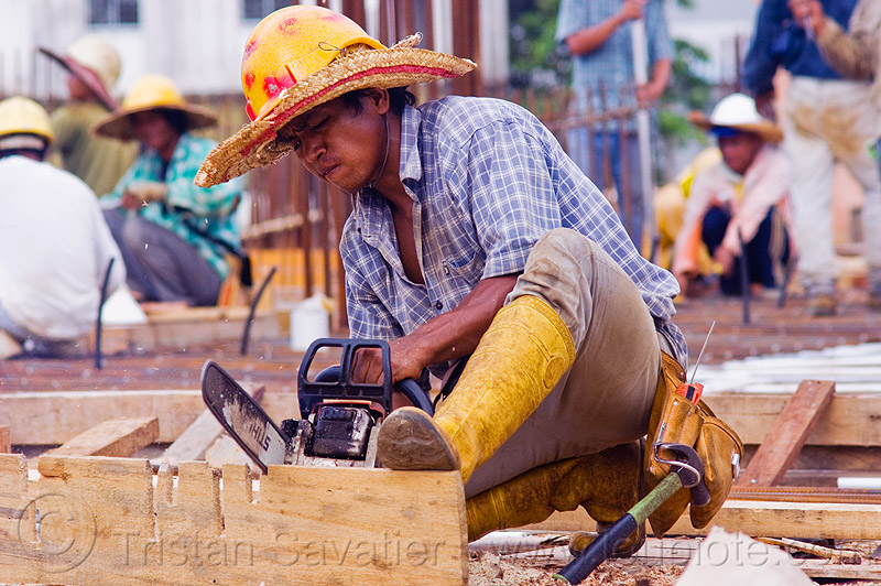construction worker cutting timber to make concrete formwork, borneo, building construction, chainsaw, concrete forms, concrete wall forms, construction site, construction workers, formwork, lumber, malaysia, man, miri, plank, rubber boots, safety helmet, straw hat, sun hat, timber, working