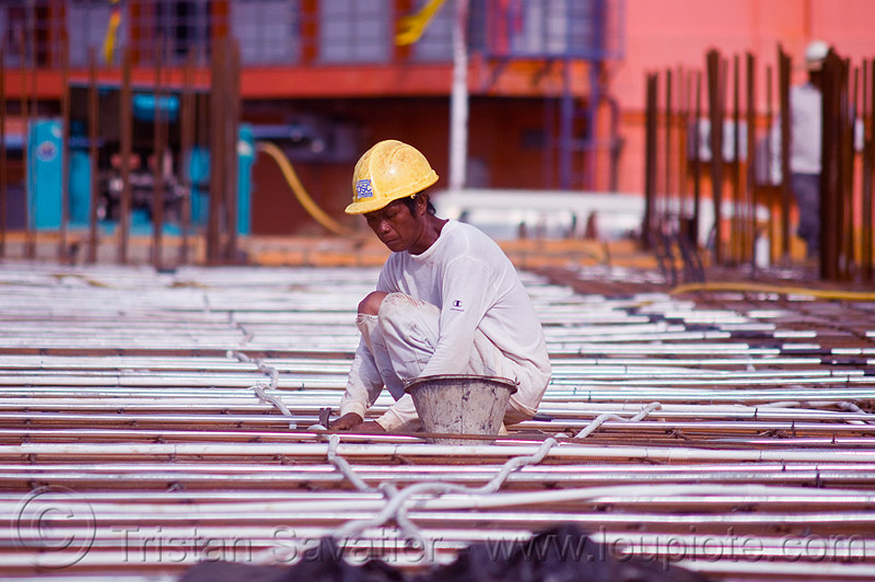 construction worker - deck formwork, borneo, bucket, building construction, concrete forms, concrete wall forms, construction site, construction workers, formwork, malaysia, man, miri, rebars, safety helmet, squating