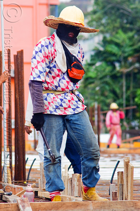 construction worker - face mask and sun hat, building construction, concrete forms, concrete wall forms, formwork, hammer, lumber, man, rebars, standing, straw hat, timber, walking