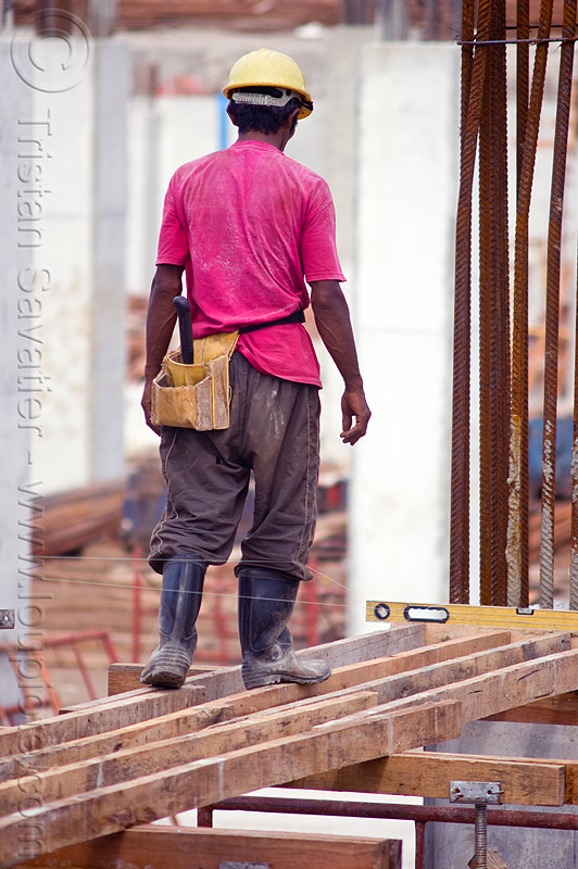 construction worker - timber shoring, borneo, bubble level, building construction, concrete forms, concrete wall forms, construction site, construction workers, formwork, lumber, malaysia, man, miri, rebars, safety helmet, scaffolding, shoring, spirit level, timber, walking