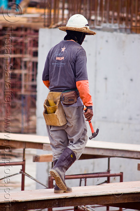 construction worker - tool pouch - hammer, borneo, building construction, construction site, construction workers, hammer, lumber, malaysia, man, miri, rubber boots, safety helmet, scaffolding, shoring, straw hat, sun hat, timber, tool belt, tool pouch, walking