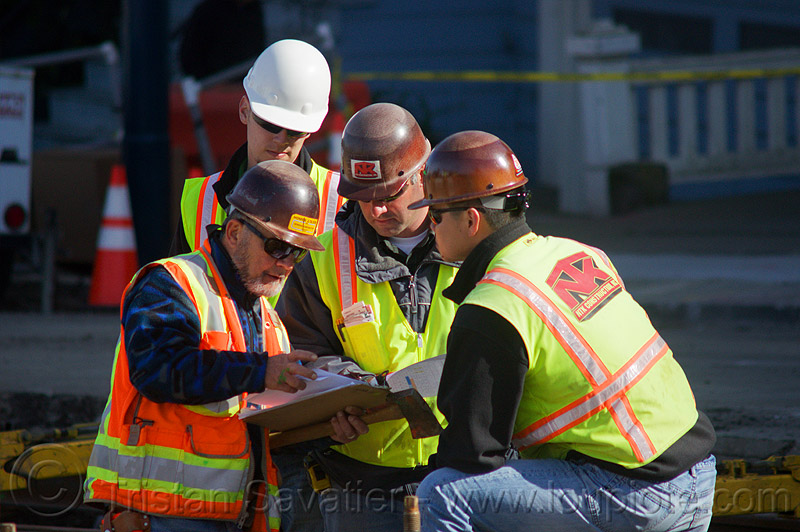 construction workers checking the project blueprint, blueprint, construction workers, duboce, foreman, foremen, high-visibility jacket, high-visibility vest, light rail, men, muni, ntk, railroad construction, railroad tracks, railway tracks, reflective jacket, reflective vest, safety helmet, safety vest, san francisco municipal railway, surveyors, track maintenance, track work, working