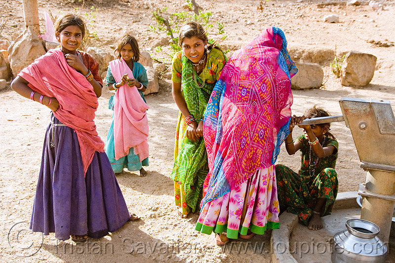 country girls pumping water - hand pump - near udaipur (india), people, saris, water pump