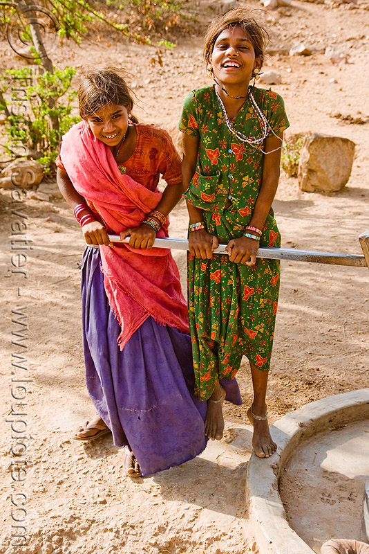 country girls pumping water with hand pump, girls, hand pump, handle, saris, two, udaipur, water pump