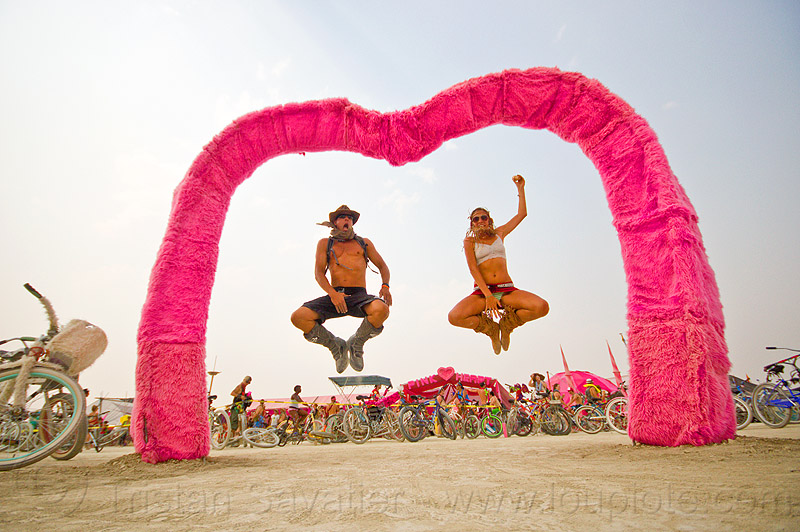 couple jumping under the pink heart - burning man 2013, couple, jump, jumpshot, man, pink heart camp, woman