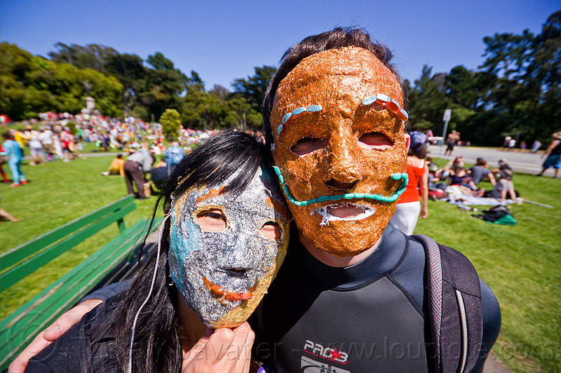 couple with silver and copper color masks, bay to breakers, couple, festival, footrace, golden gate park, green moustache, green mustache, man, masks, moustaches, mustaches, street party, turf, woman