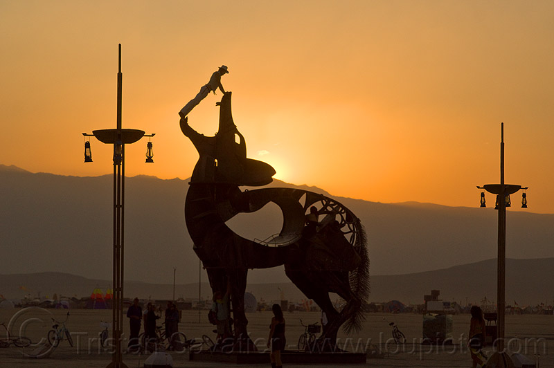 coyote sculpture by bryan tedrick - burning man 2013, art installation, bryan tedrick, burning man, climbers, climbing, coyote sculpture, dusk, metal sculpture, statue, sunset
