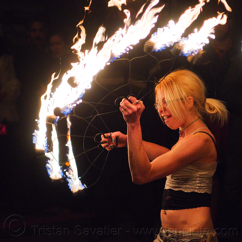 cressie mae with fire fans, american steel studios, cressie mae, fire dancer, fire dancing, fire fans, fire performer, fire spinning, flames, holidays in flux, night, oakland, poplar gallery, spinning fire, woman