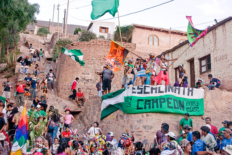 crowd celebrating carnival in the street - carnaval de tilcara (argentina), andean carnival, banner, carnaval, comparsa, crowd, flags, los caprichosos, noroeste argentino, parade, quebrada de humahuaca, stairs, tilcara