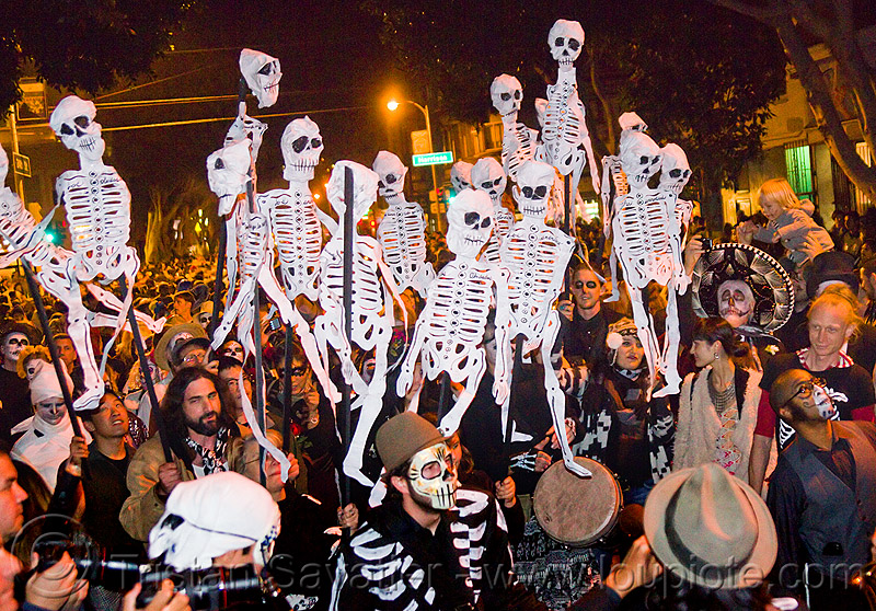 dancing paper skeleton puppets, crowd, dancing skeletons, day of the dead, dia de los muertos, halloween, music, musicians, night, paper skeletons, people, procession, street