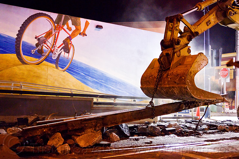 demolition of muni tracks in front of the bike mural at  church and duboce, bicycle mural, bike mural, bucket attachment, caterpillar, chain, demolition, excavator bucket, heavy equipment, light rail, machinery, muni, night, ntk, railroad construction, railroad tracks, rails, railway tracks, san francisco municipal railway, track maintenance, track work