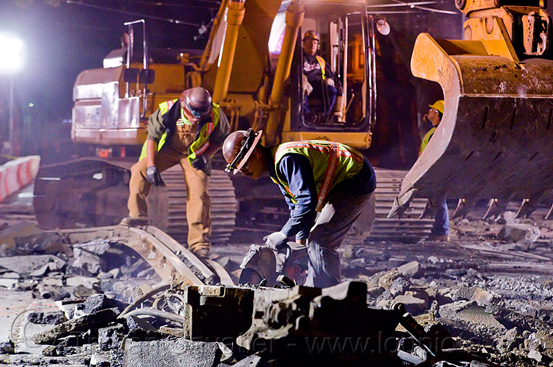 demolition of municipal railway tracks, abrasive saw, bucket attachment, caterpillar, cut-off saw, cutting, demolition, excavator bucket, heavy equipment, high-visibility jacket, high-visibility vest, light rail, machinery, men, muni, night, ntk, power tool, railroad construction, railroad tracks, rails, railway tracks, reflective jacket, reflective vest, safety helmet, safety vest, san francisco municipal railway, track maintenance, track work, workers