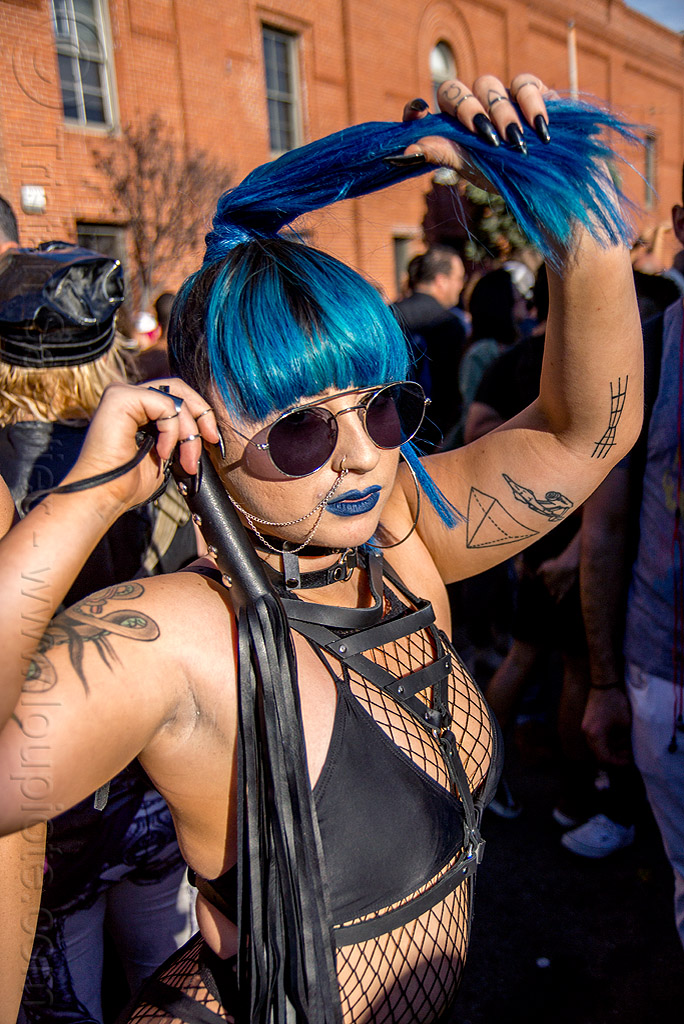dominatrix with whip - folsom street fair 2015 (san francisco), arm tattoos, blue hair, fashion, fishnet top, leather whip, nose chain, nose piercing, nostril piercing, ponytail, sunglasses, woman