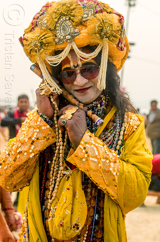 drag queen hindu guru in yellow costume and decorated turban - kumbh mela (india), beads, costume, decorated, dressed-up, finger rings, flute, guru, headdress, hindu pilgrimage, hinduism, india, maha kumbh mela, makeup, man, necklaces, standing, sunglasses, tilak, turban, yellow