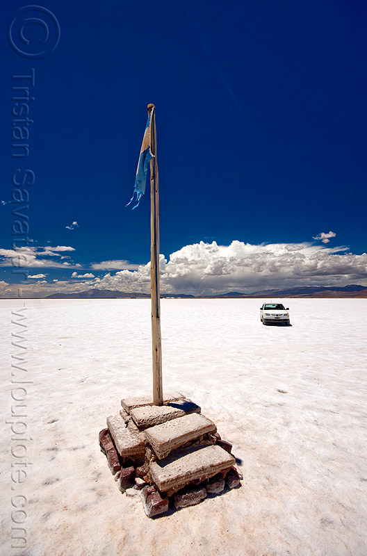 driving on a salt flat - salinas grandes - salar (argentina), blue sky, car, desert, flag, flag pole, halite, horizon, jujuy, noroeste argentino, people, rock salt, salt bed, salt flats, salt lake, white