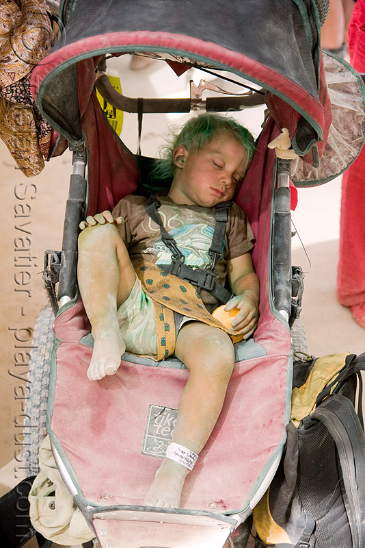 dusty kid in stroller - green hair - burning man 2008, center camp, child, dusty, green, kid, sitting, sleeping, stroller