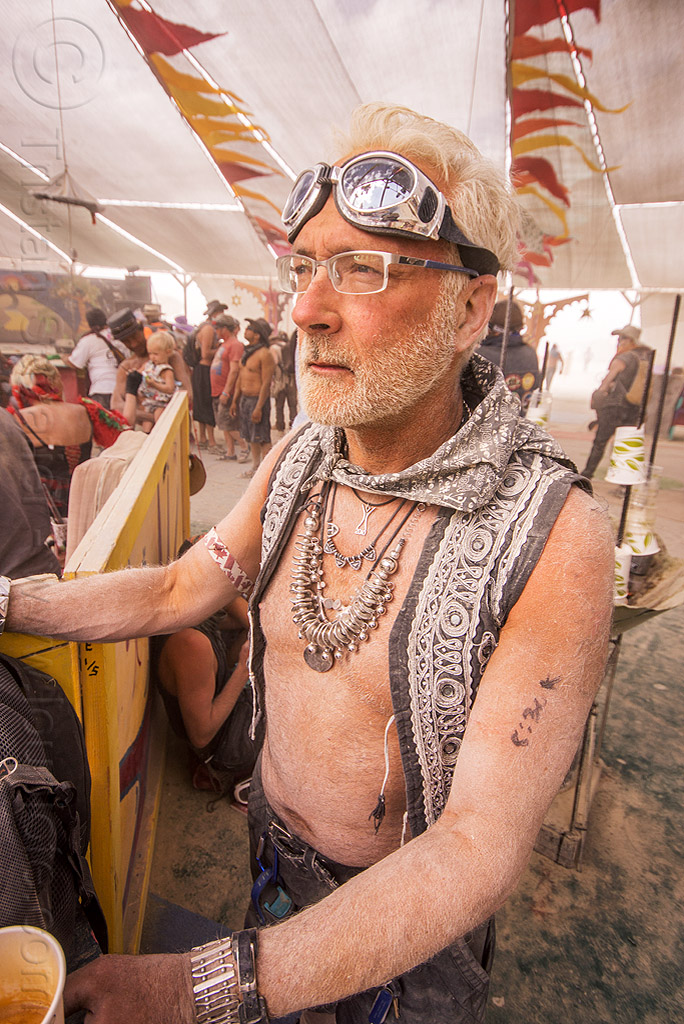 dusty man gazing at center camp - burning man 2015, burning man, dusty, goggles, metal necklace, prescription glasses, spectacles, white hair
