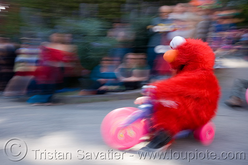 "elmo racing at the BYOBW - ""bring your own big wheel"" race - toy tricycles (san francisco), big wheel, drift trikes, elmo costume, moving fast, potrero hill, race, red, sesame street costume, speed, speeding, toy tricycle, toy trike, trike-drifting"