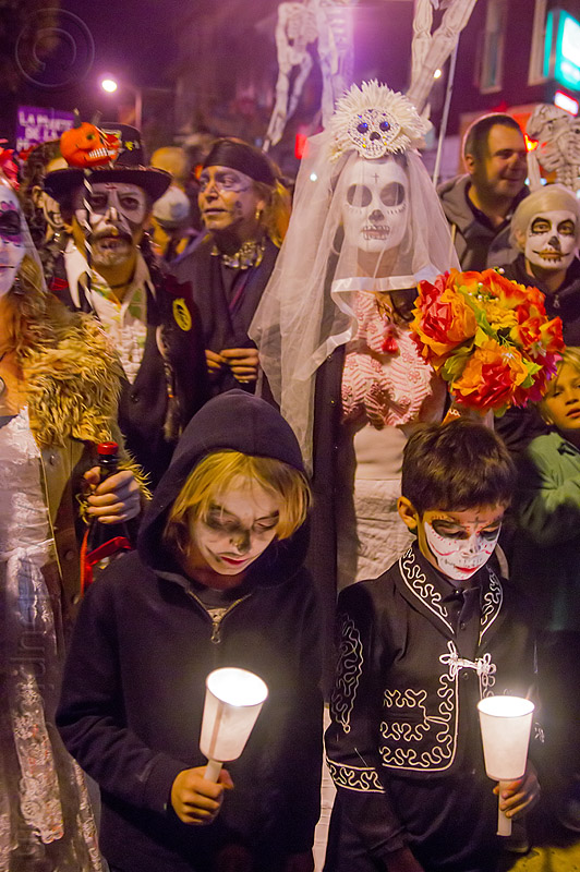 family at dia de los muertos procession, bride, candles, children, couple, day of the dead, dia de los muertos, face painting, facepaint, family, flowers, groom, halloween, kids, night, procession, sugar skull makeup, white veil, woman