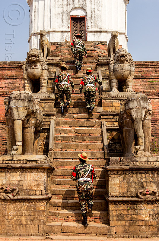 fasidega temple - nepali gurkha army soldiers walking up steps - bhaktapur durbar square (nepal), bhaktapur, durbar square, elephants, fatigues, gorkhas, guards, gurkha army, gurkha regiment, gurkhas, hat, hindu temple, hinduism, men, military, nepalese army, red stripe, sculptures, soldiers, stairs, statues, steps, stone elephant, stone lions, uniform, walking