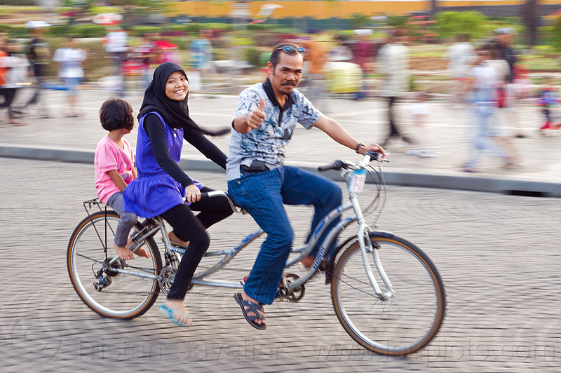father and daughters riding tandem, child, daughters, family, father, girl, hijab, islam, jakarta, java, kid, man, medan merdeka, merdeka square, moving, muslim, park, riding, road, tandem bicycle, tandem bike, thumb up, woman