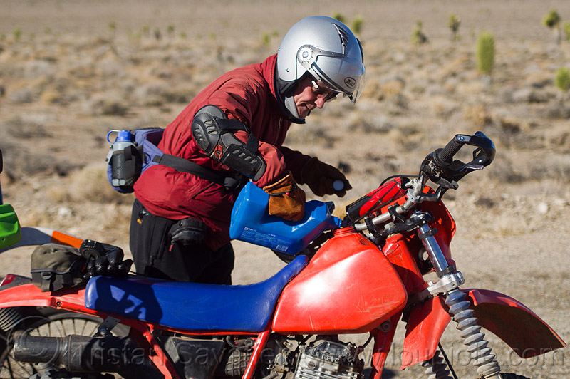 filling the tank of the dirt motorbike, death valley, desert, filling-up, fuel, gas tank, gasoline, honda, jerrycan, man, motorbike touring, motorcycle helmet, motorcycle touring, mototbike, petrol, plastic can, pouring, xr 350