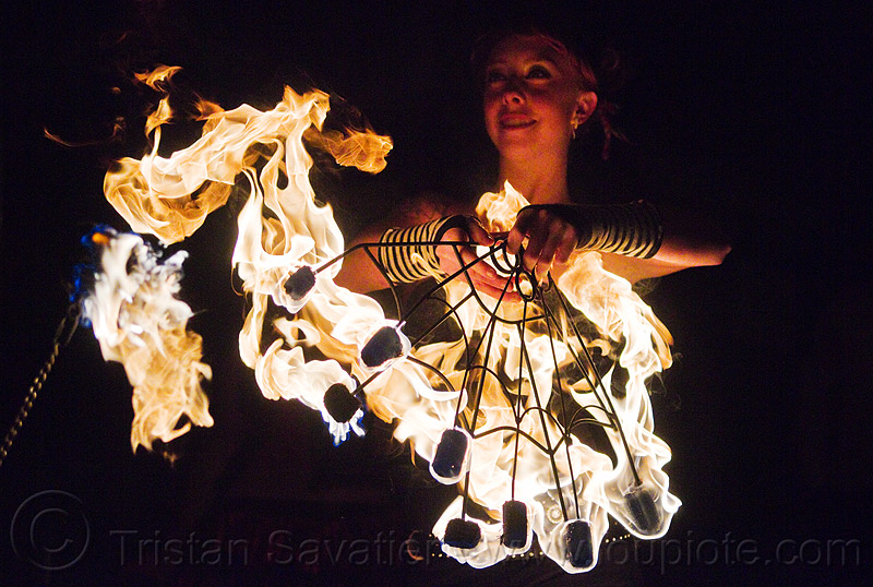 fire performer with fire fans, american steel, american steel studios, fire dancer, fire dancing, fire spinning, flames, holidays in flux, night, oakland, people, poplar gallery, samantha, spinning fire, woman