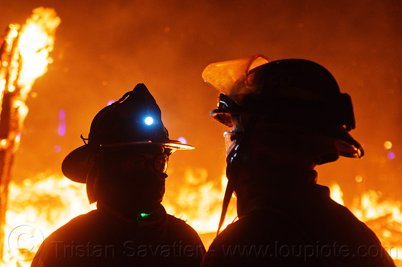 firefighters near the fire - the man is burning - - burning man 2012, backlight, burning man, fire proximity suit, firefighters, head light, headlamp, helmets, night of the burn, silhouettes, the man, visor
