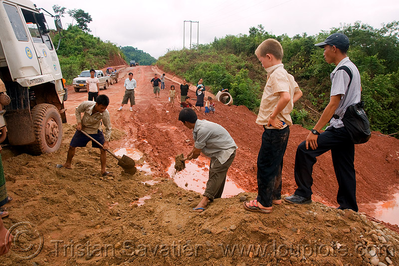 fixing the road with shovels (laos), lorry, men, mud, road, ruts, shoveling, shovels, tracks, truck